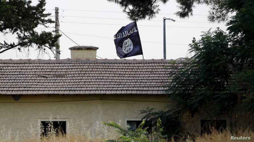 FILE - An Islamic State flag flies over the customs office of Syria's Jarablus border gate as seen from the Turkish town of Karkamis, in Gaziantep province, Turkey, Aug. 1, 2015.