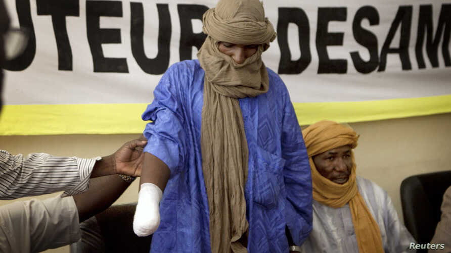 A victim of forced hand amputation by al-Qaida-linked Islamist group Movement for Unity and Jihad under Sharia law as punishment for stealing livestock, Alhader Ag Mahamoud, 30, attends a news conference organized by Amnesty International in Bamako,