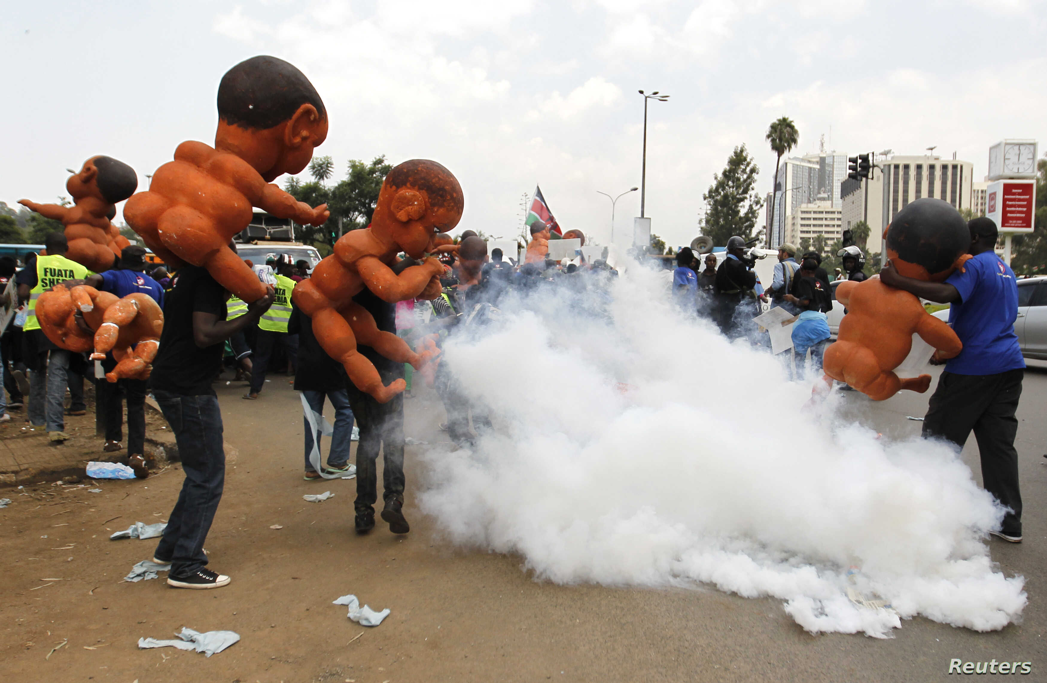 """Protesters carrying giant baby models run away after riot police fired tear gas to disperse them during a march dubbed """"Kenya ni Kwetu"""" in Kenya's capital Nairobi, Feb. 13, 2014."""
