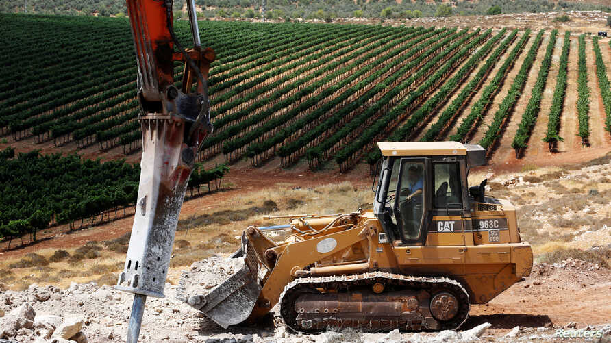A man operates a bulldozer on a field as work begins on the construction of Amichai, a new settlement which will house some 300 Jewish settlers evicted in February from the illegal West Bank settlement of Amona, in the West Bank, June 20, 2017.