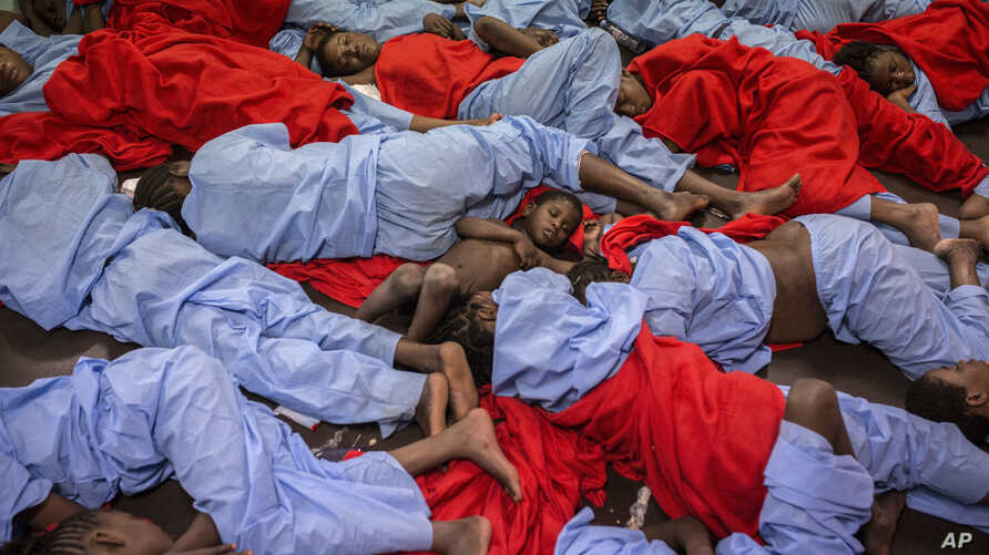 FILE - In this Friday Jan. 13, 2017 photo, Idris 3, from Mali, center, sleeps next to his mother Aicha Keita, right, on the deck of the 'Golfo Azzurro' vessel after being rescued from the Mediterranean sea, about 20 miles north of Ra's Tajura, Libya.
