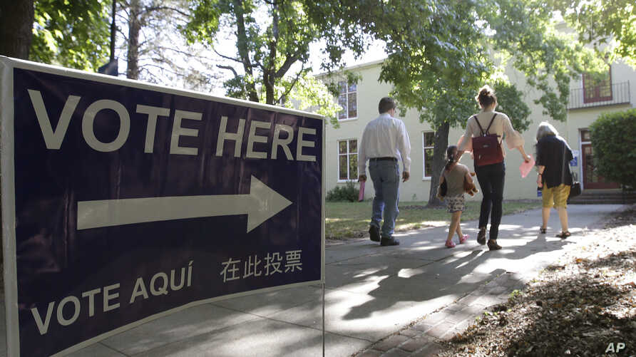 FILE - Voters walk to a precinct place at the Sierra 2 Center for the Arts and Community to cast their ballots, June 5, 2018, in Sacramento, Calif.