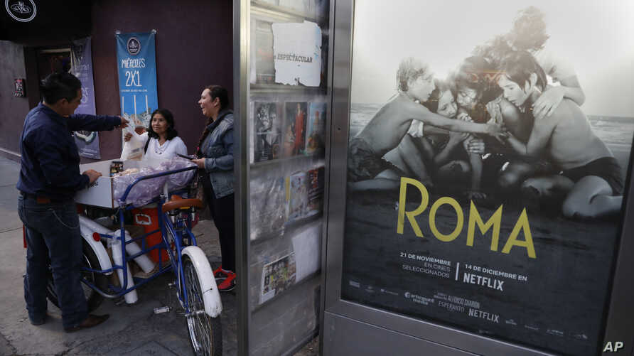 """Women buy pastries and sandwiches from a bicycle vendor in the Roma Sur neighborhood of Mexico City, Wednesday, Dec. 19, 2018, near a newspaper kiosk where Alfonso Cuaron's film """"Roma"""" is advertized."""