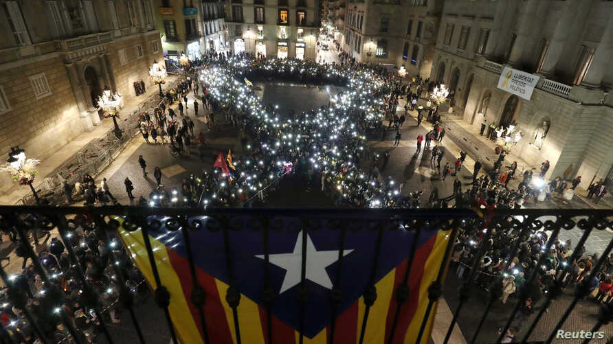 People form a ribbon during a demonstration called by pro-independence associations asking for the release of jailed Catalan activists and leaders at Sant Jaume square in Barcelona, Spain, Nov. 16, 2017.