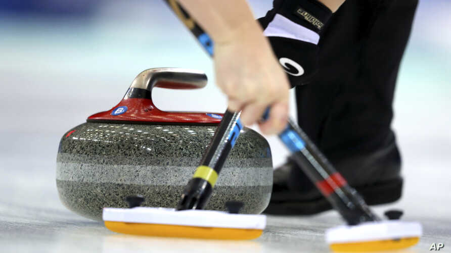 FILE - Members of Scotland's team sweep a path for the stone during their match against Sweden in the CPT World Women's Curling Championship 2017 in Beijing, China, March 25, 2017.