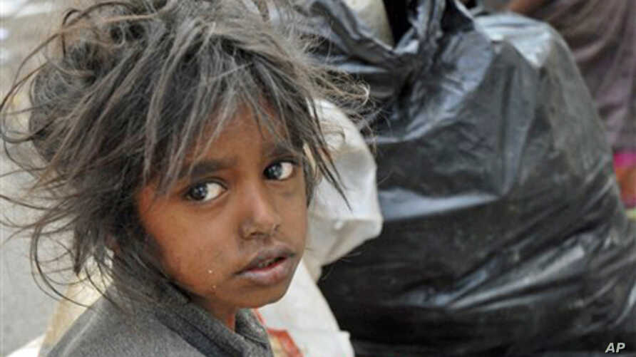 A child sits in front of a garbage dump on World Poverty Day in Hyderabad, India, 17 October 2007 (FILE).