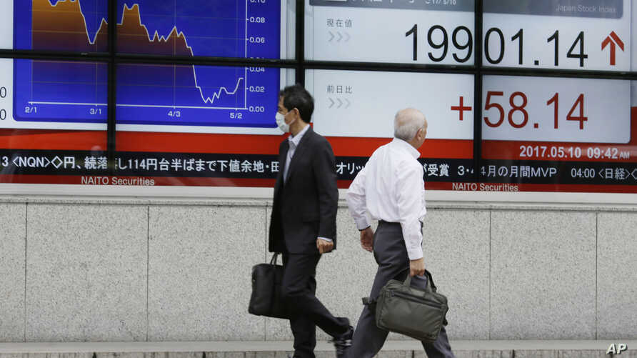 FILE - Men walk past an electronic stock board showing Japan's Nikkei 225 index at a securities firm in Tokyo, May 10, 2017.