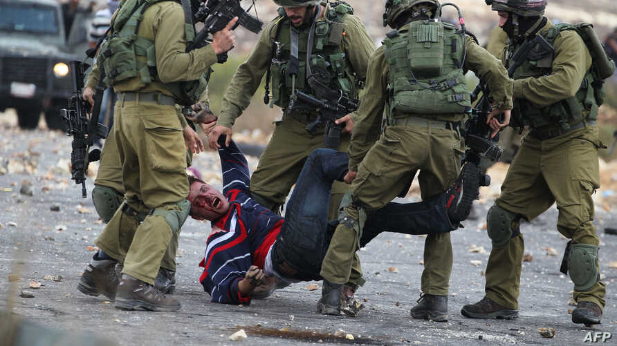 Israeli soldiers detain a wounded Palestinian stone thrower after infiltrated members of the Israeli security forces shot at fellow protesters during clashes in Beit El, on the outskirts of the West Bank city of Ramallah, on October 7, 2015.