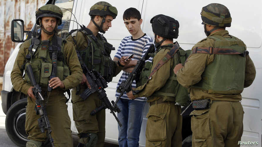 Israeli soldiers search a Palestinian youth during an operation to locate three Israeli teens in the West Bank city of Hebron, June 16, 2014.