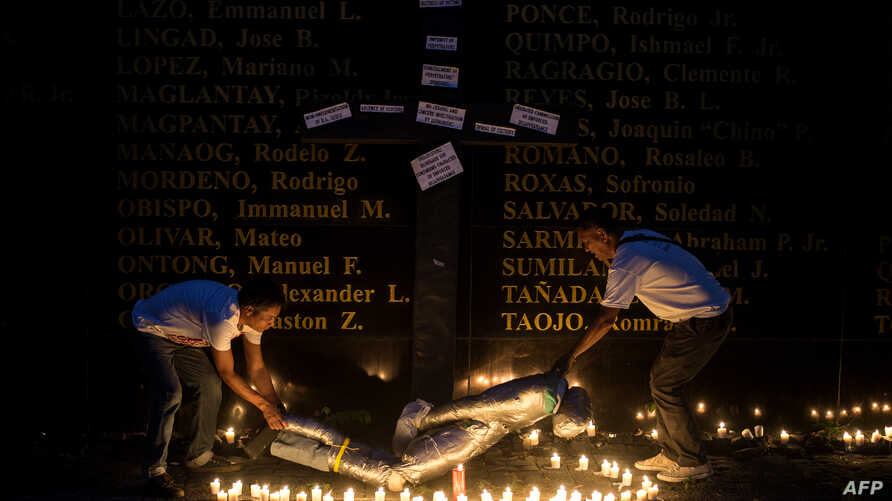 People lift a mock victim during a prayer vigil in support of the families of victims of extra-judicial killings in Manila on April 12, 2017.