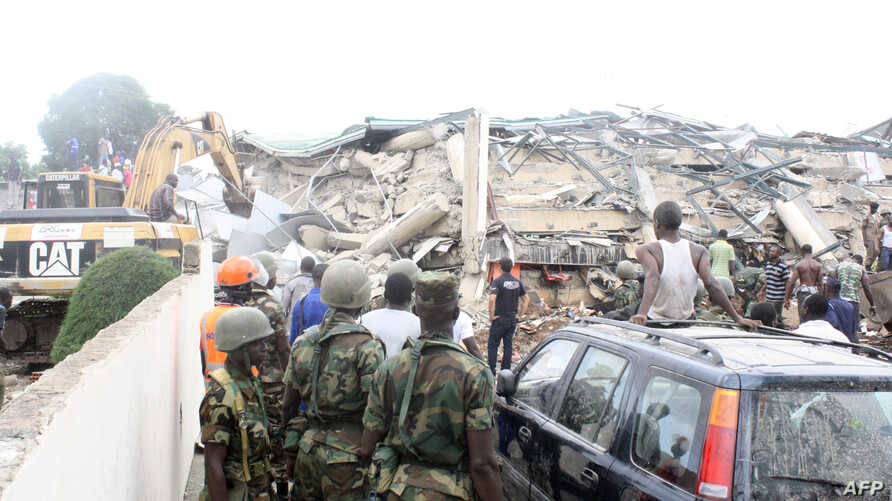 People look at an excavator clearing the rubble on the scene of a six-story shopping center that collapsed in Accra, November 7, 2012.