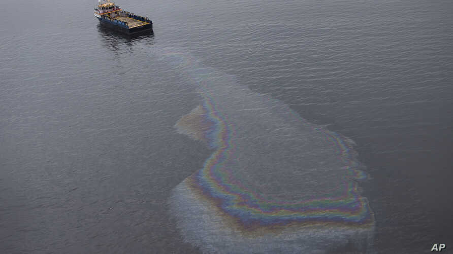 FILE - This aerial view shows a boat leaking oil in the waters near Rio de Janeiro, Brazil. In Seattle, a jury convicted a fisherman of similarly dumping oily pollution into the Pacific Ocean.