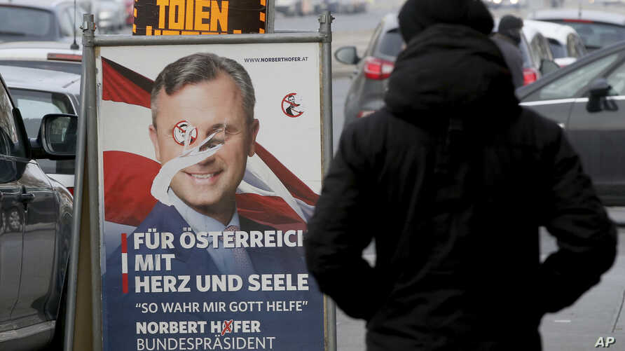 A man passes a defaced campaign poster of far-right presidential candidate Norbert Hofer in Vienna, Austria, Dec. 5, 2016. Centrist Alexander Van der Bellen defeated Hofer in Sunday's election, a win welcomed by moderate politicians across Europe.