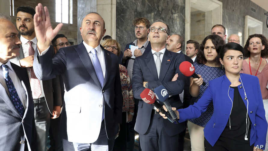 Turkey's Foreign Minister Mevlut Cavusoglu (2nd-L) talks to German Foreign Minister Heiko Mass (C-R) during a visit to a section of the Turkish parliament, damaged during the failed July 15, 2016 coup attempt, in Ankara, Turkey, Sept. 5, 2018.