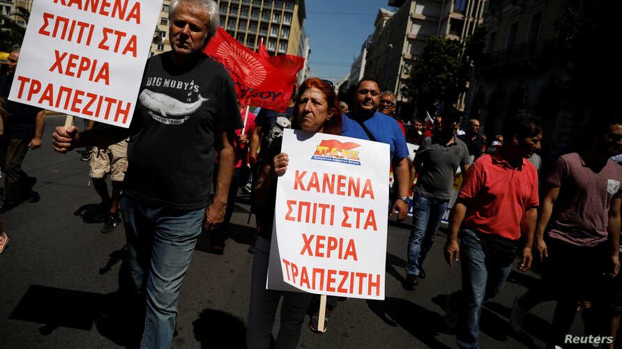 "Members of the communist-affiliated PAME take part in a demonstration marking a general strike against against planned austerity measures in Athens, May 30, 2018. The placards read ""No house to the hands of bankers."""