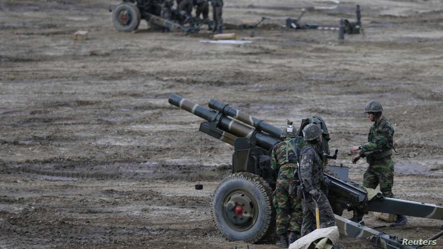 FILE - South Korean soldiers of an artillery unit check their armaments during a military drill near the demilitarized zone separating North Korea from the South, in Paju, north of Seoul.