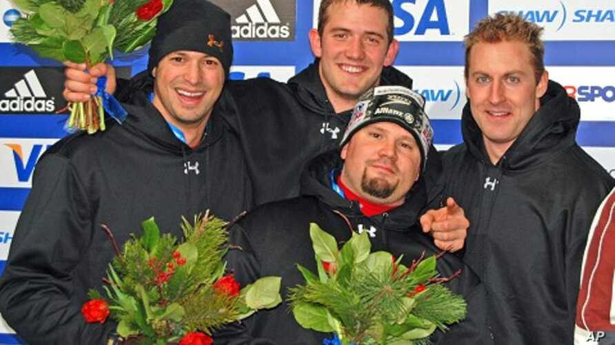 Steve Holcomb, bottom center, with bobsled crew members on the trophy stand