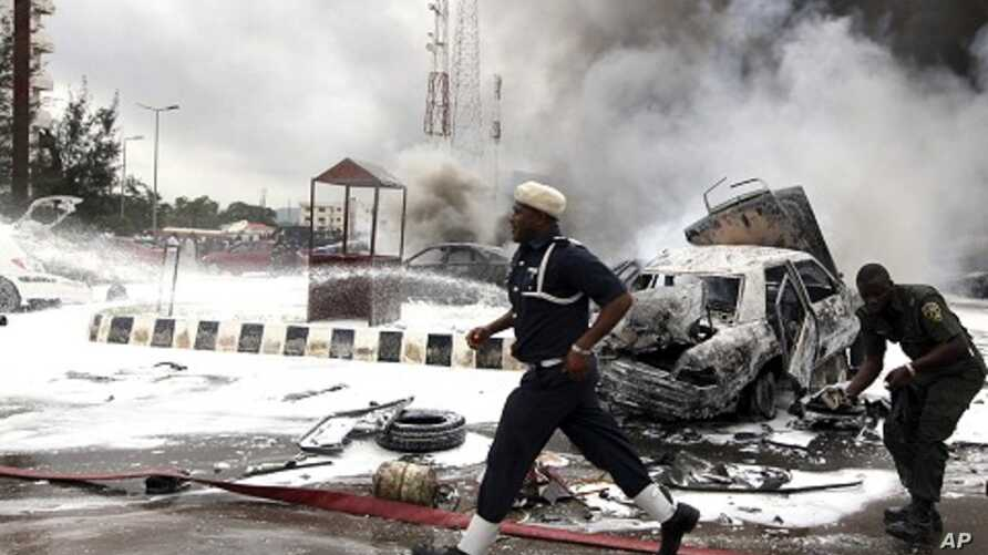 Members of emergency services work at the scene of an explosion at a police station after a suspected suicide bomber was killed and many vehicles were destroyed in Abuja, June 16, 2011