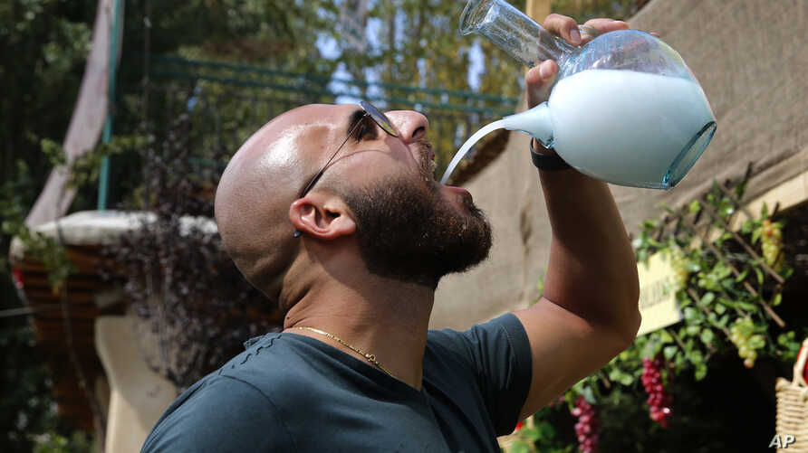 In this Sept. 8, 2018 photo, a Lebanese man drinks arak from a traditional glass pitcher during a festival that celebrates Lebanon's national alcoholic drink, in the town of Taanayel, east Lebanon.