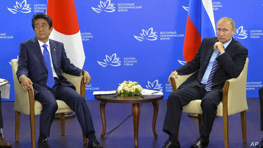 Russian President Vladimir Putin, right, and Japanese Prime Minister Shinzo Abe pose for a photo during their meeting in Vladivostok, Russia, Sept. 2, 2016.