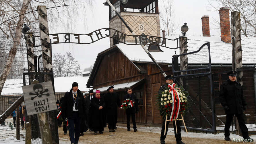 """People arrive to lay wreaths at the """"death wall"""" at the former Nazi German concentration and extermination camp Auschwitz, during the ceremonies marking the 74th anniversary of the liberation of the camp and International Holocaust Victims Remembranc"""