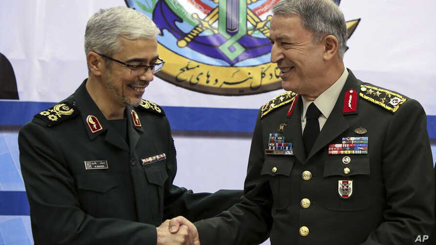 Turkey's Chief of Staff Gen. Hulusi Akar, right, and Iran's Chief of Staff of Armed Forces, Gen. Mohammad Hossein Bagheri, shake hands after a meeting in Tehran, Iran, Oct. 2, 2017.