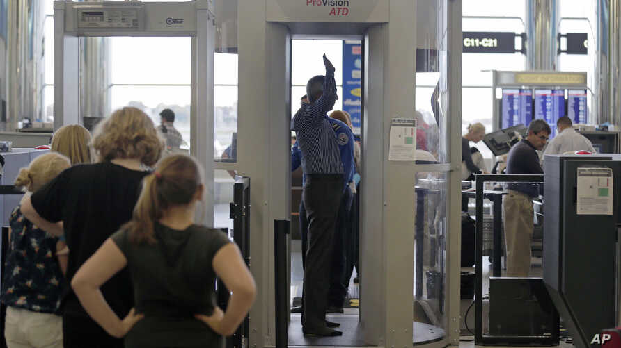 FILE - Passengers are scanned at a Terminal C security checkpoint at Logan Airport in Boston using a millimeter wave body scanner.