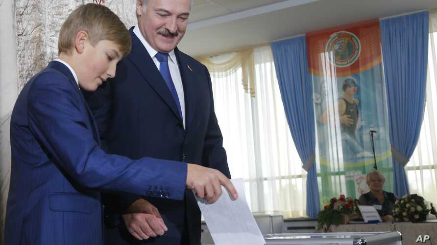Belarusian President Alexander Lukashenko with his youngest son Nikolai casts his ballot at a polling station, during the presidential election, in Minsk, Belarus, Sunday, Oct. 11, 2015.