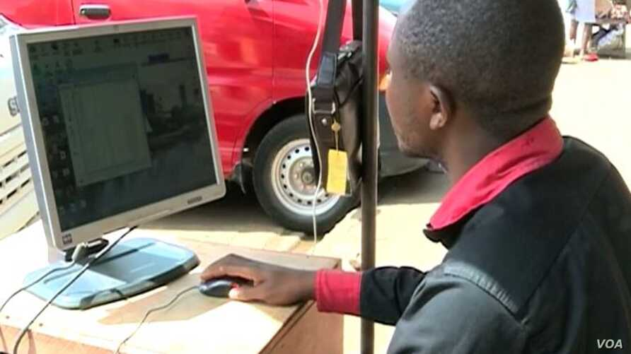 An internet service provider in Bamenda, Cameroon, uploads photos to social media after the three-month internet blackout was lifted. (Moki Edwin Kindzeka/VOA)