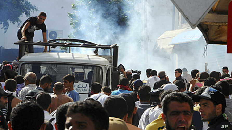 Radical Islamist militants leave as police use tear gas during a demonstration in Tunis, Tunisia, October 14, 2011.
