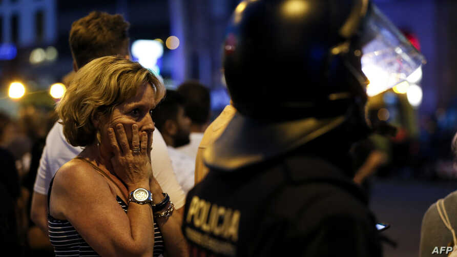 A woman gestures as she is escorted by Spanish policemen outside a cordoned off area, after a van struck members of a crowd on Las Ramblas in Barcelona, Aug. 17, 2017.