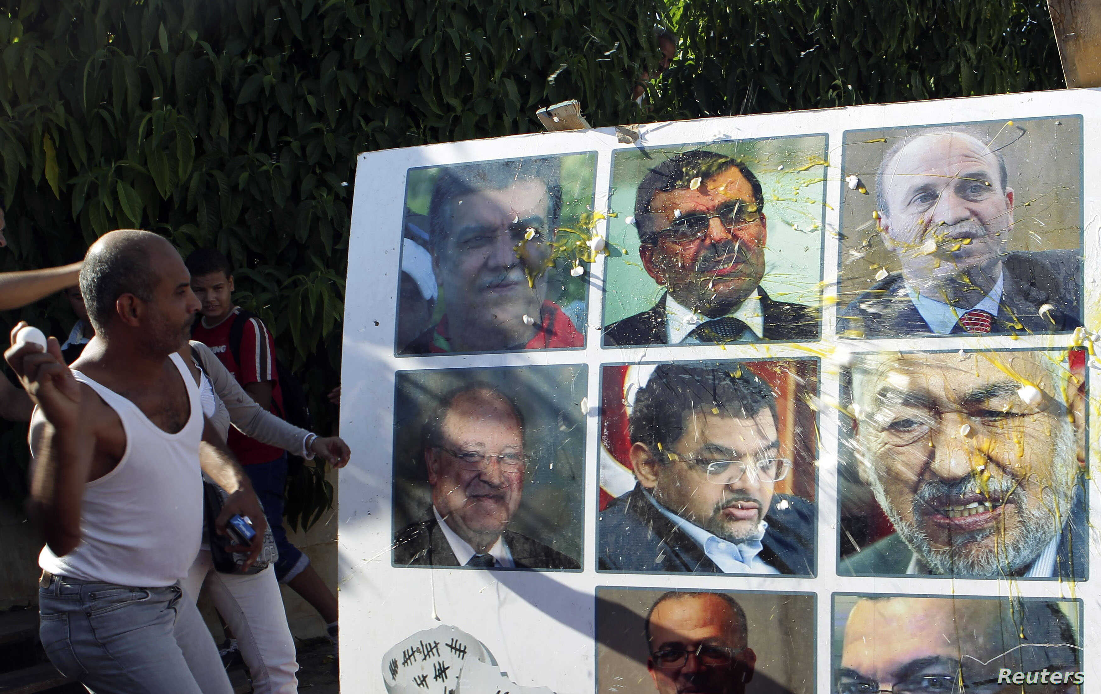 An anti-government protester throws an egg at a poster of Tunisian politicians, including Prime Minister Ali Larayedh (top row, C) and leader of the Islamist Ennahda movement Rached Ghannouchi (centre row, R) during a demonstration in Tunis October 2