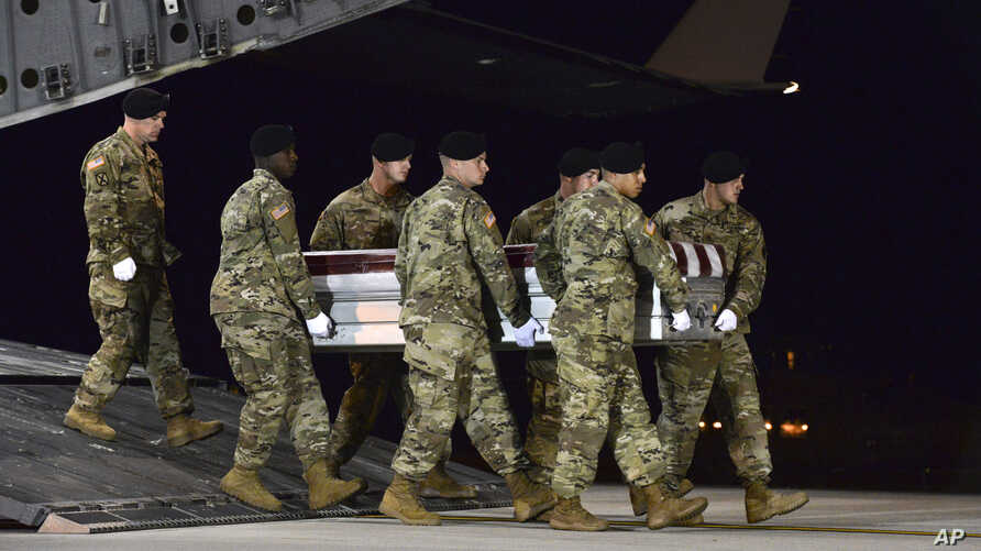 In this image provided by the U.S. Air Force, a U.S. Army carry team transfers the remains of Army Staff Sgt. Dustin Wright of Lyons, Georgia, Oct. 5, 2017, upon arrival at Dover Air Force Base, Delware.  Wright, 29, was one of four U.S. troops and f...