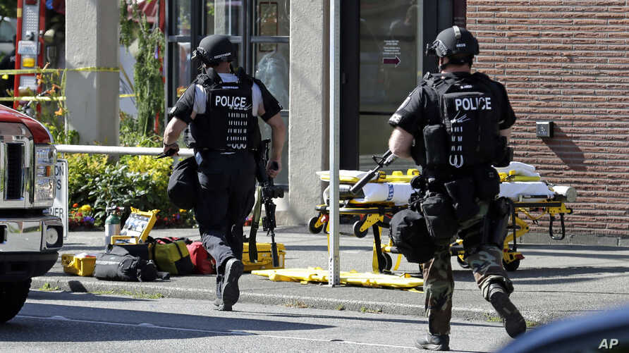 Seattle Police run toward a campus building following a shooting at Seattle Pacific University, June 5, 2014.