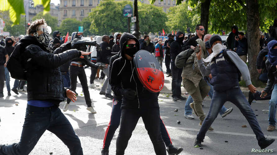 Masked youths face off with French police during a demonstration against the French labor law proposal in Paris, France, as part of a nationwide labor reform protests and strikes, April 28, 2016.