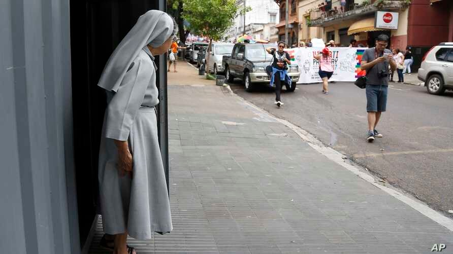 FILE - A nun looks out as the the annual LGBT parade files past, in Asuncion, Paraguay, Sept. 30, 2017.