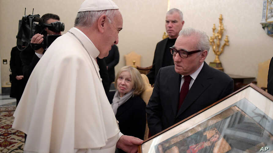 "Pope Francis looks at a painting given to him as a gift from director Martin Scorsese, right, on the occasion of their private audience at the Vatican, Wednesday, Nov. 30, 2016.  Francis has met with Scorsese, whose new film, ""Silence,"" about Jesuit"