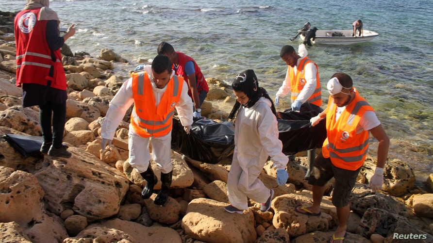 Rescue workers carry a bag containing the dead body of a migrant that washed ashore in Tripoli's Janzour city, Libya, Nov. 5, 2016.