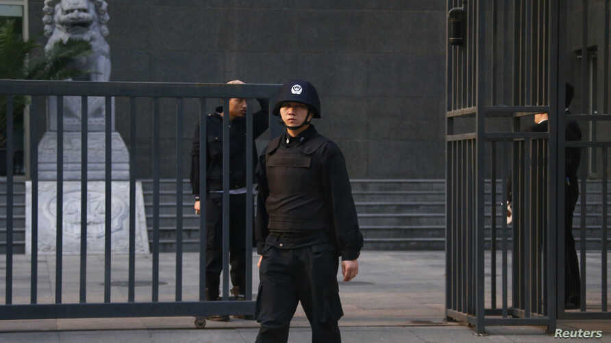 Security personnel stand guard outside as Chinese human rights lawyer Ding Jiaxi stands trial at a court in Haidian District, Beijing, April 8, 2014.