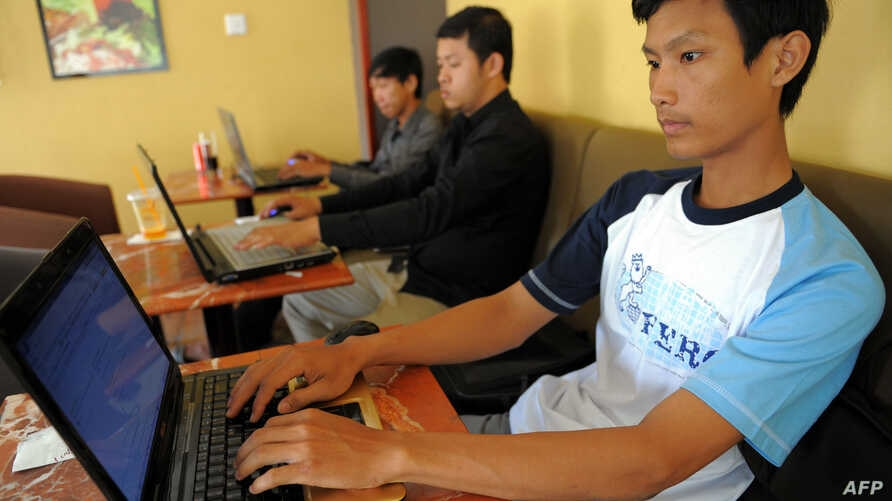 FILE - Cambodian men use the internet at a cofee shop in Phnom Penh.