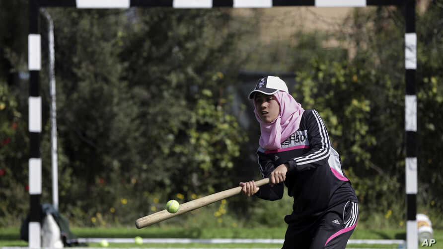 Palestinian women train for an all-women's baseball game on a soccer field in Khan Younis, southern Gaza Strip, March 19, 2017.