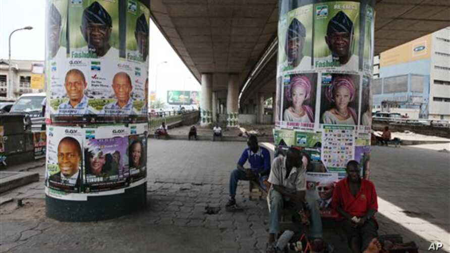 Men take a rest under a bridge pasted with election posters in Lagos, Nigeria, March 30, 2011