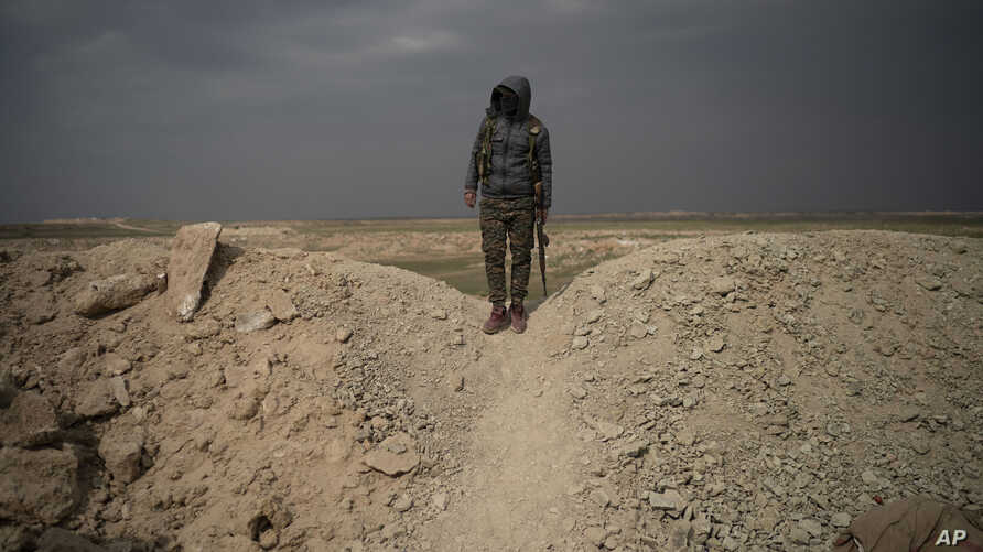 A U.S.-backed Syrian Democratic Forces (SDF) fighter stands atop a hill in the desert outside the village of Baghouz, Syria, Thursday, Feb. 14, 2019.