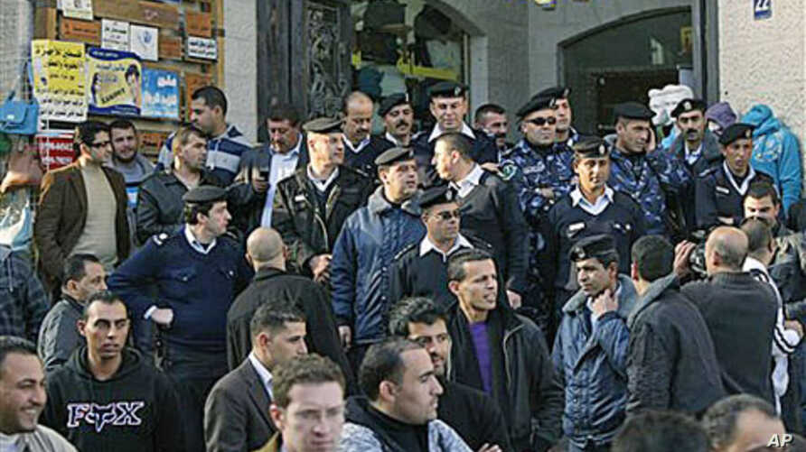 Palestinian police officers block the entrance to the Al-Jazeera TV office, after protesters vandalized it, in the West Bank city of Ramallah, 24 Jan 2011
