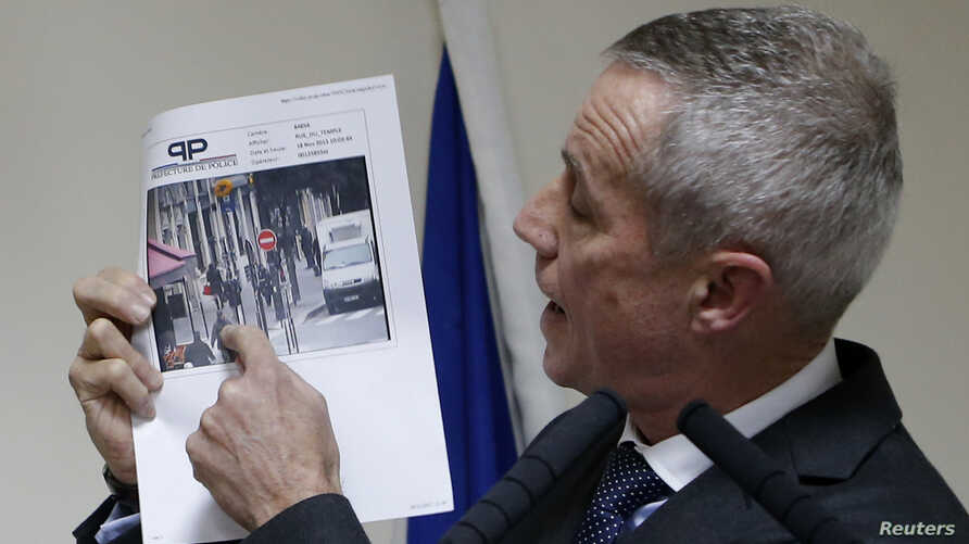 Paris prosecutor Francois Molins shows one of the two photographs of the suspect gunman taken from surveillance footage during a news conference in Paris, Nov. 18, 2013.