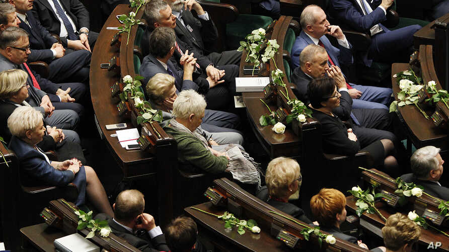Poland's opposition lawmakers and senators with white roses, the symbol of their protest against the government policies, during a speech by President Andrzej Duda in parliament in Warsaw, Poland, Dec. 5, 2017.