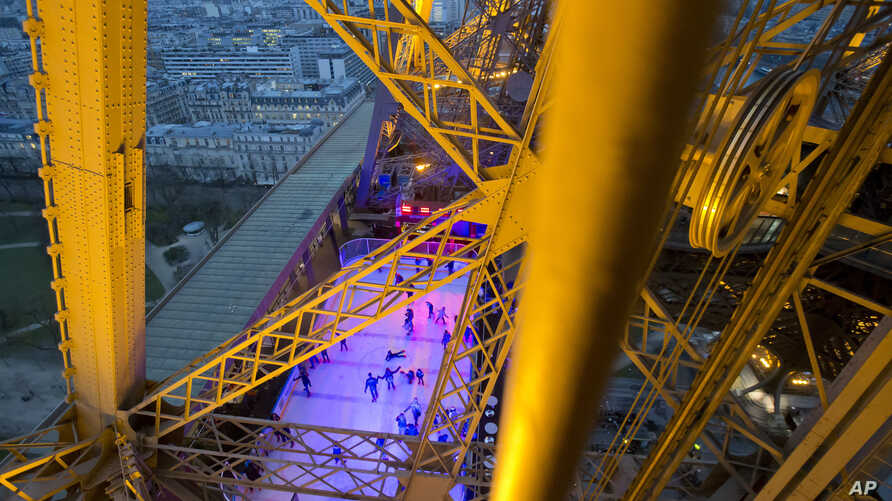 People skate on the ice rink set at 57 meters (188 feet) above the ground on the Eiffel Tower in Paris. Tourism to Paris is showing signs of revival after a yearlong slump attributed to deadly extremist attacks, violent labor protests, strikes and fl