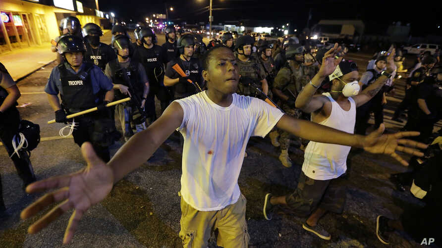 People are moved by a line of police as authorities disperse a protest in Ferguson, Mo. early Wednesday, Aug. 20, 2014. On Saturday, Aug. 9, 2014, a white police officer fatally shot Michael Brown, an unarmed black teenager, in the St. Louis suburb.