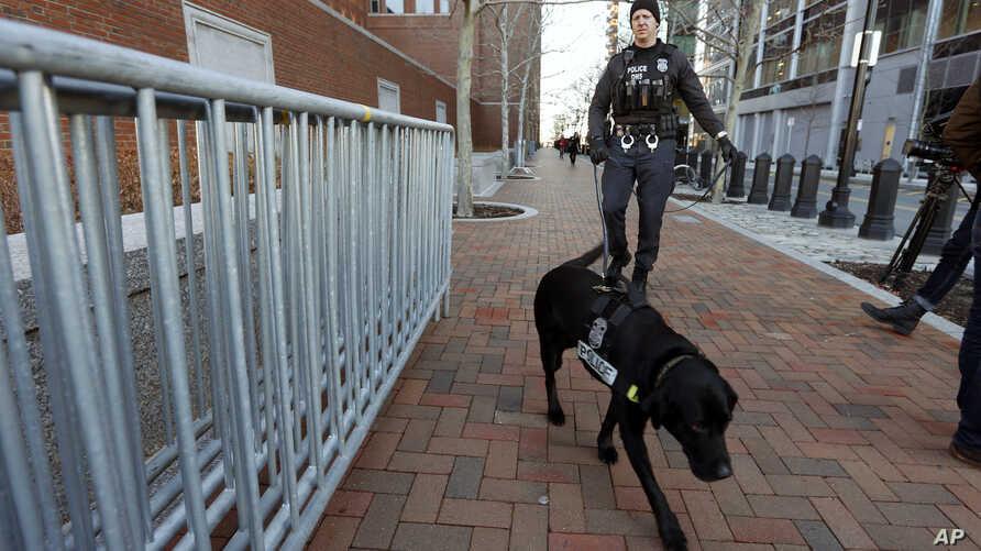 A federal police officer and K-9 dog patrol outside the federal courthouse in Boston, Monday, Jan. 5, 2015, for the first day of jury selection in the trial of Boston Marathon bombing suspect Dzhokhar Tsarnaev. (AP Photo/Michael Dwyer)