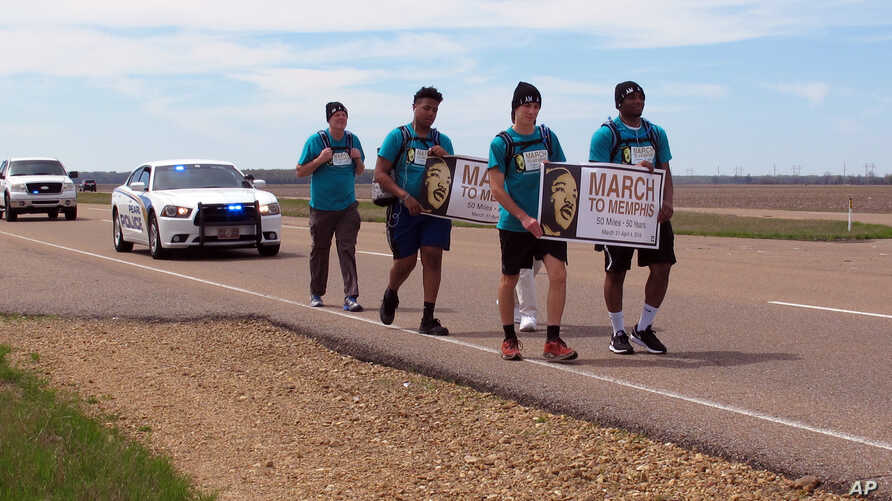 A group of teenagers and adults from Mississippi walk along U.S. Highway 61 on their 50-mile march to Memphis, Tennessee, as a tribute to slain civil rights leader Martin Luther King Jr., March 31, 2018, in Dundee, Miss. The group plans to attend eve